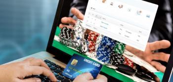 Läppäri, jonka edessä käsi pitelemässä pankkikorttia